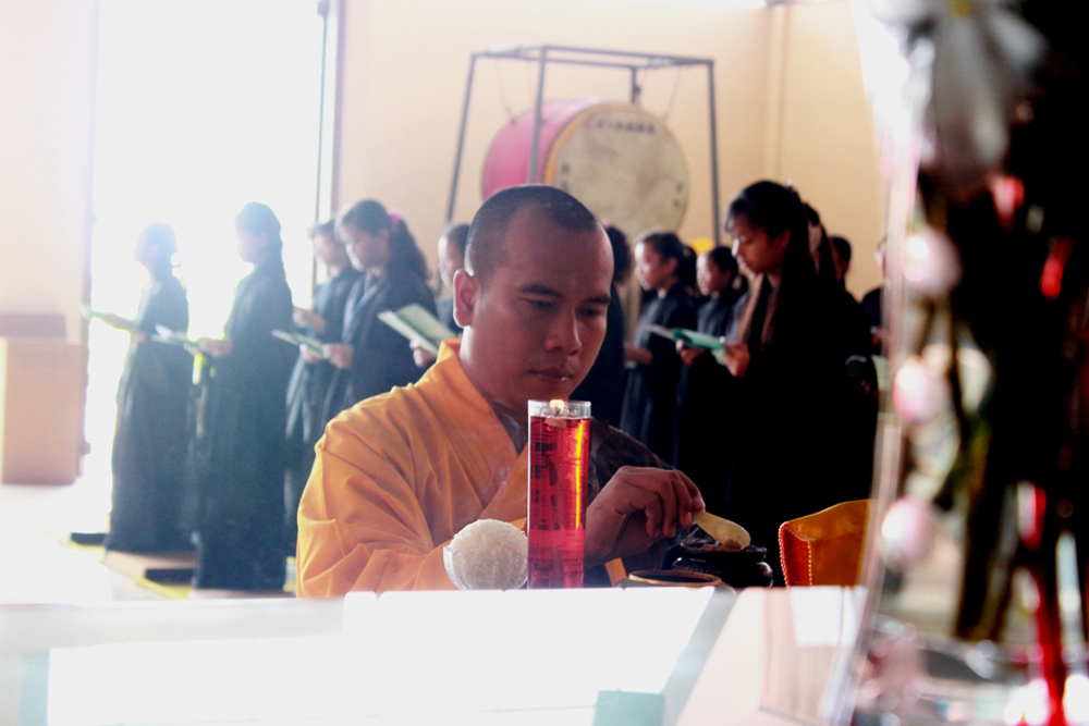 Bhiksu pembimbing menyalakan pelita